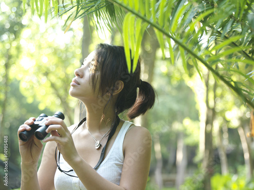 Young woman in tropical forest, holding binoculars