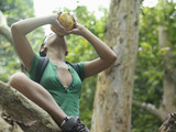 Young woman in tropical forest drinking from coconut, low angle view