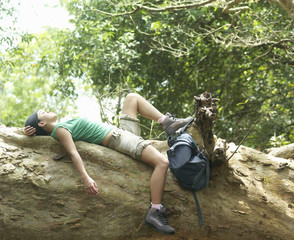 Young woman resting on rock formation in forest, side view