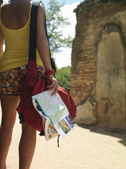 Young woman looking at ancient ruins, holding guide book, back view, mid section