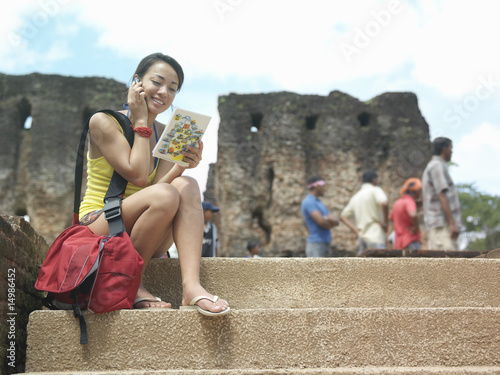Young woman sitting on steps, talking on mobile phone, holding guide book