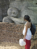 Young woman looking at statue of sleeping Buddha, side view