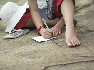 Young woman sitting on rock, writing, low section