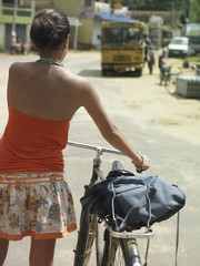 Young woman on street, walking with bicycle, back view