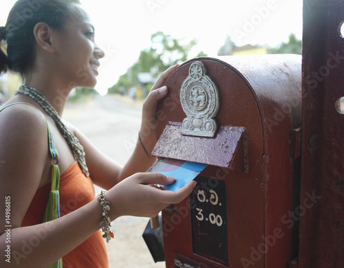 Young woman putting postcard to mailbox, smiling