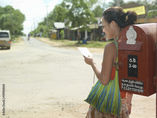 Young woman standing by mailbox reading postcard