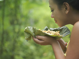 Young woman holding food on leaf, smelling it