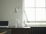 Desk with laptop, lamp and jug of water