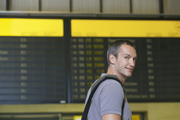Traveller in front of flight status board in airport