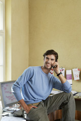 Young man sitting on desk using phone in office