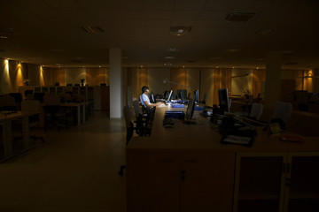 Woman working at laptop in dark office