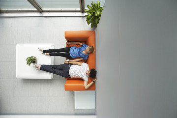 Two people reclining on couch in reception room, view from above