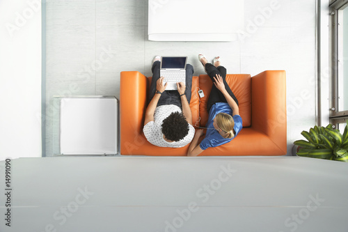 Two people using laptop in reception room, view from above