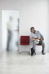 Young man listening to two people talking behind door