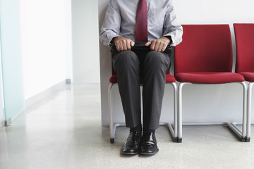 Man waiting on chair in corridor, low section