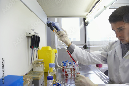 Scientist filling test tube with hi-tech pipette in laboratory