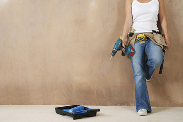 Woman with toolbelt and drill leaning against wall, low section