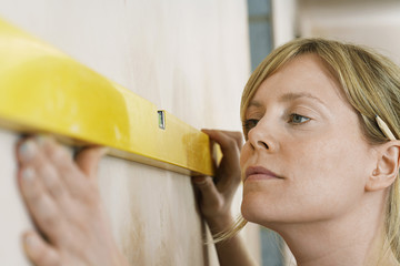 Woman using spirit level, close-up