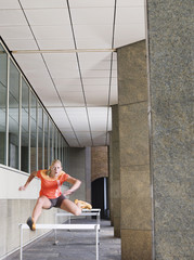 Woman jumping hurdles outside building