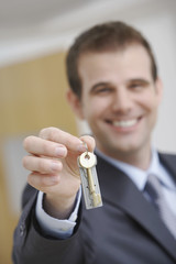 Real estate agent holding key, indoors