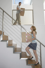 Couple carrying boxes upstairs in new home