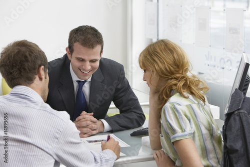 Couple with real estate agent in office, man writing