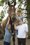 Mother and children 5-6, 7-9 with horse outdoors, portrait