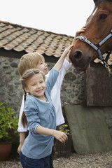 Sister and brother 5-6, 7-9 stroking horse outside stable