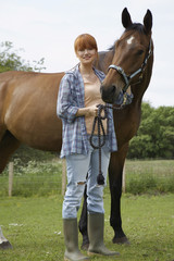 Woman with horse in field, portrait