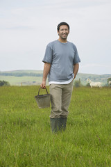 Man holding bucket in field, portrait