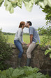 Couple kissing on wall in countryside