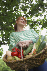 Woman holding fruit and vegetable basket, outdoors