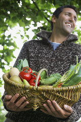 Man holding fruit and vegetable basket, outdoors