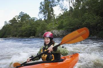 Woman kayaking in river
