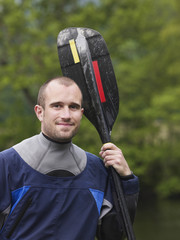 Man with kayak paddle, outdoors, portrait