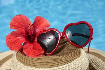Gafas de sol y sombrero al lado de una piscina azul