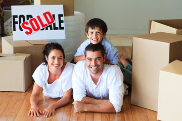 Family in their new house lying on floor with boxes