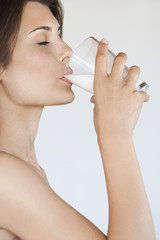 Young woman drinking milk, side view