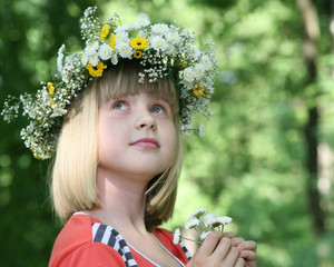 Portrait of the girl in a flower wreath.