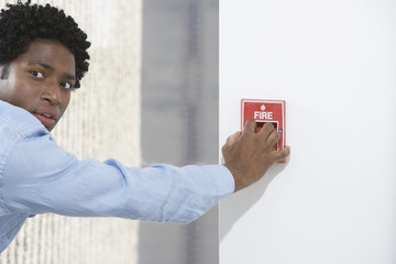 Man starting fire alarm, indoors