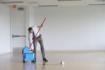 Business man using mop in empty room