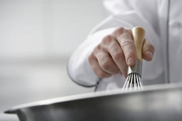 Chef mixing ingredients in bowl, close-up