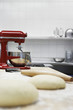 Dough on wooden board, beside dough mixer in kitchen