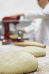 Chef using dough mixer in kitchen, focus on dough in foreground
