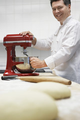 Chef using dough mixer in kitchen, portrait