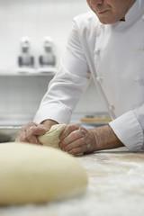 Chef preparing dough in kitchen
