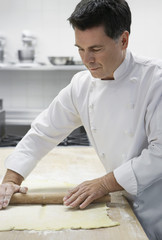 Chef rolling dough in kitchen