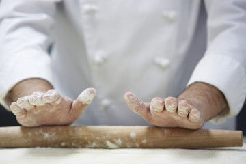 Chef rolling dough using rollingpin, close-up