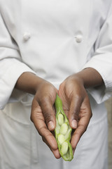 Female chef holding vegetables, mid section