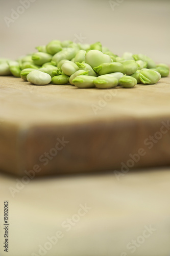 Fresh broad beans on wooden board, close-up